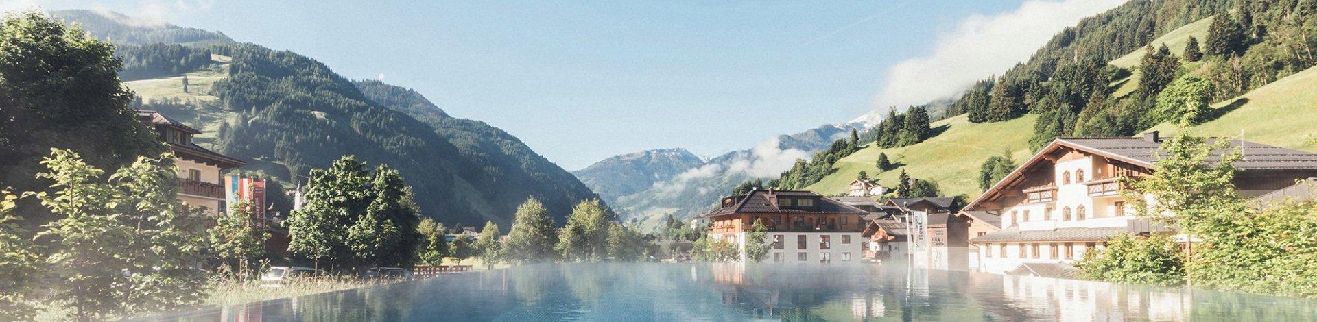 Wellnesshotels Österreich: Außenansicht vom Hotel Nesslerhof mit Pool und Blick in die Berge