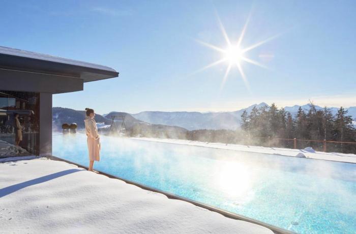 Winterurlaub & Wellness: Hier zu sehen der dampfende Außenpool im Hotel Chalet Mirabell, davor eine Frau im Bademantel auf schneebedeckter Terrasse.