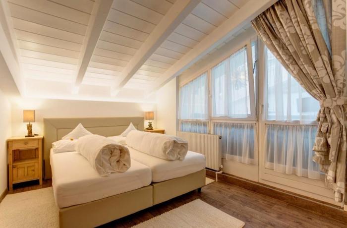 Zimmeransicht mit Bett und Deckenschräge im Am Dorfplatz Suites - Adults only in St. Anton am Arlberg – Tirol, Österreich