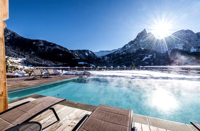 Einzigartige Skihotels: Außenpool mit Blick auf verschneite Berge im Sonus Alpis, Trentino Südtirol, Italien