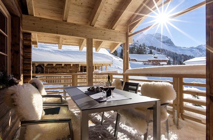 Einzigartige Skihotels: Hotelzimmerterrasse mit Tisch und fellbezogenen Stühlen im Aadla Walser Chalets, Vorarlberg, Österreich