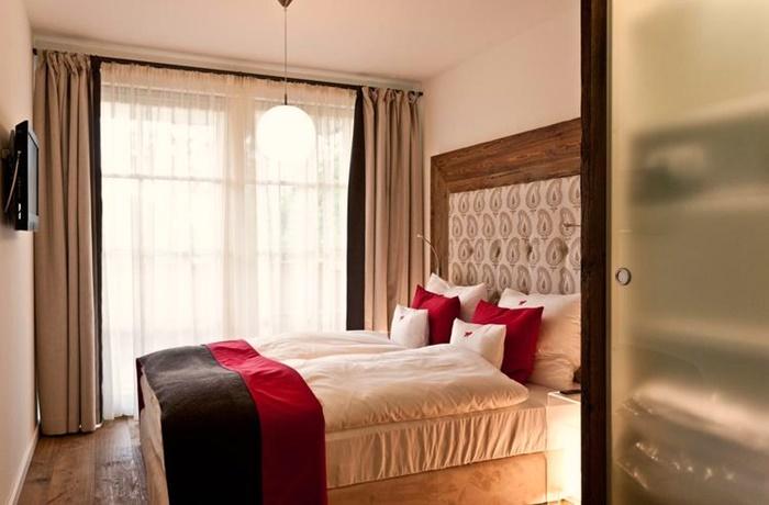 Zimmer mit Boxspringbett und einer Mischung aus roten, schwarzen und weißen Farben, Holzboden und Holzrahmen