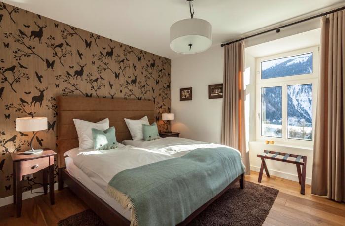 Gemütliche Zimmer mit Bett und Fensterblick auf die Berge im Hotel Bellevue Wiesen in Graubünden,