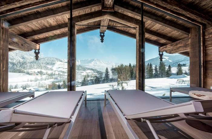Wellnesshotels: Puradies Hotel & Chalets in Leogang, Österreich mit Blick aus dem Panoramafenster auf verschneite Landschaft
