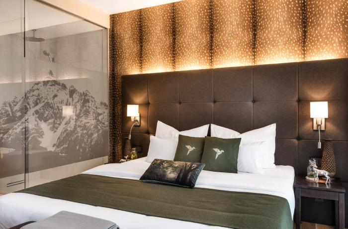 Zimmeransicht im Hotel dasMEI mit einem Bett vor goldener Wand.