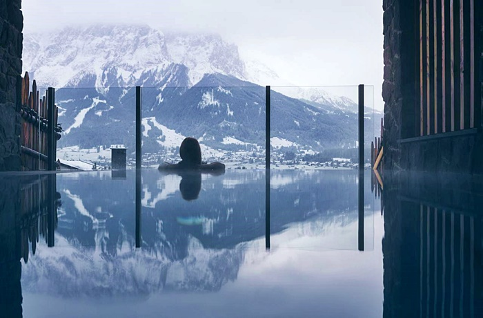 Wellnesshotels: Pure Lermoos - Tirol, Österreich mit Rückenansicht von einer Frau im Pool und Blick auf Berge