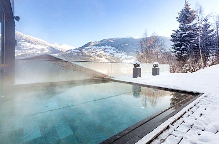 Einzigartige Skihotels: Dampfender Außenpool in Schneelandschaft im Hotel Das Kaltenbach, Tirol, Österreich