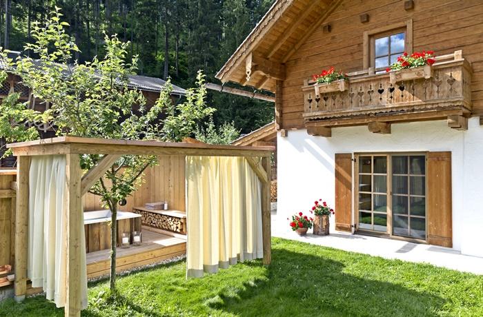 Die Chalets im Feriendorf Holzlebn haben freistehende Badewannen im Garten.