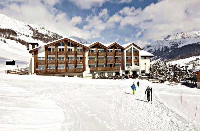 Einzigartige Skihotels: Skifahrer laufen zur Piste direkt am Hotel Lac Salin Spa & Mountain Resort, Lombardei, Italien