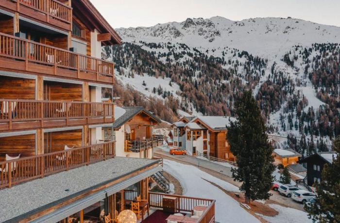 Blick auf das Chandolin Boutique Hotel, daneben verschneite Bergkulisse.