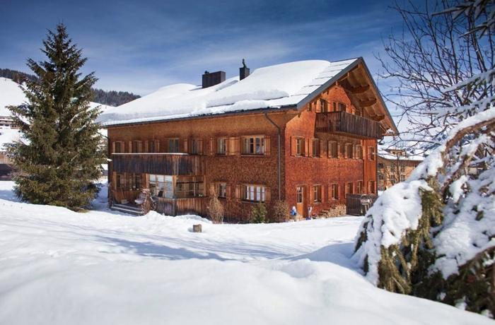 Die wundervoll verschneite, rustikale Hausfront des Alpina Lech NATURAL LIVING