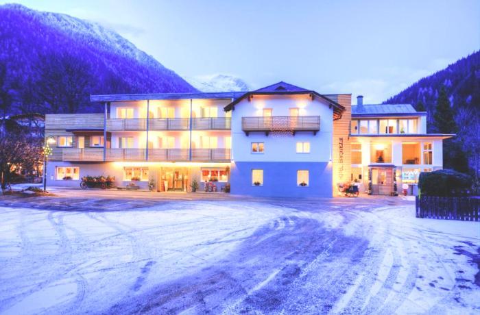 Außenansicht vom hell erleuchteten Hotel Bergkristall in Abenddämmerung vor Schneekulisse.
