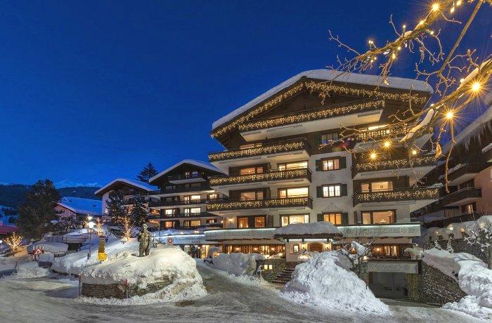 Blick auf das erleuchtete Hotel Alpina Klosters in Graubünden am Abend.