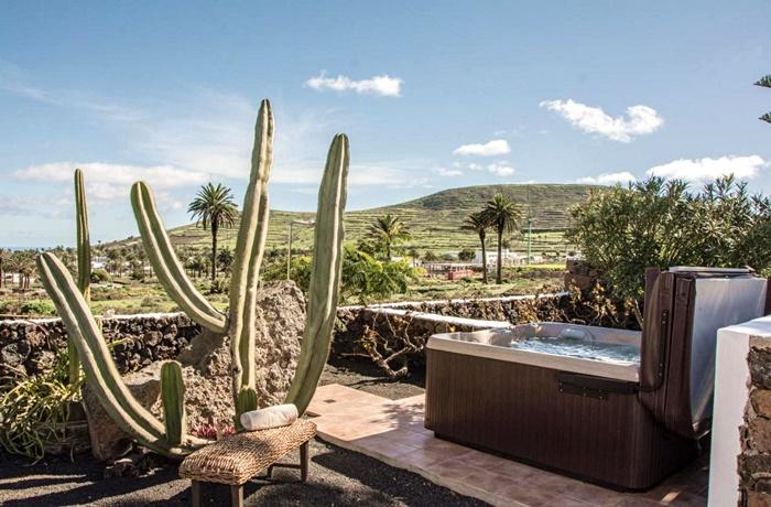 """Hotels in Spanien: Finca """"La Picolisima"""", Haría, Terrasse mit Jacuzzi, Panoramablick auf Stadt und Berglandschaft, Palmen und blauer Himmel"""