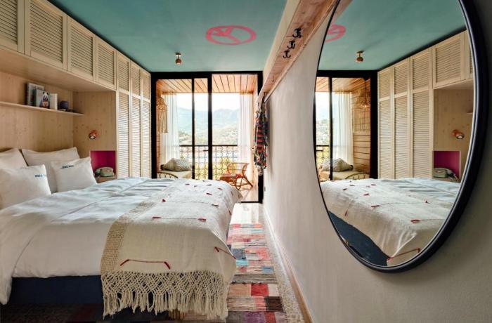 Buntes Zimmer mit rundem Spiegel und türkisfarbener Decke samt Peace-Zeichen im Bikini Island & Mountain Port de Soller auf Mallorca
