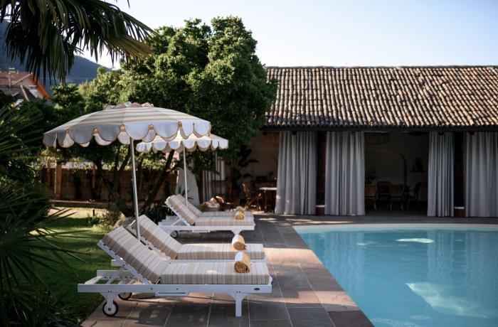 Sonnenliegen mit Schirm am Pool des Adults Only Hotels Villa Arnica, Trentino Südtirol, Italien