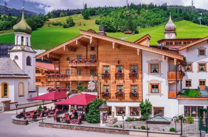 Außenansicht vom Hotel Gaspingerhof mit Holzfassade und Blick auf die Alm dahinter.