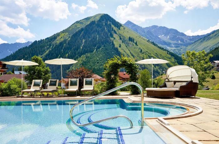 Außenpool und Blick auf Berge im Hotel Singer – Relais & Châteaux in Berwang