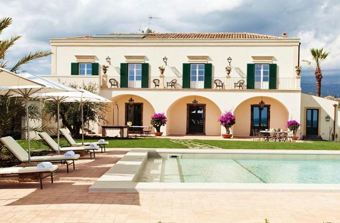 Urlaub auf Sizilien: Garten mit Pool und Hotel Boutique Resort Donna Carmela im Hintergrund
