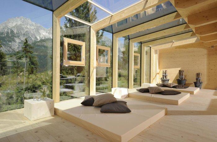 Wellnesshotels in Österreich: Ruhebereich mit großen Fenstern im Holzhotel Forsthofalm in Leogang