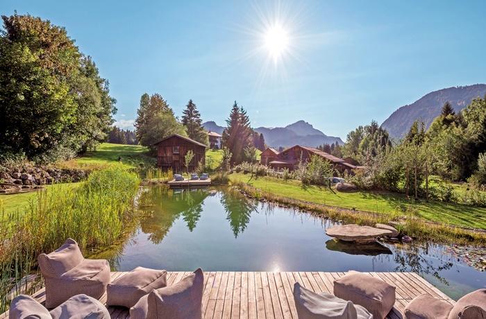 Kurzurlaub über Ostern: Naturbadeteich mit Blick auf die Berge im Hotel Oberstdorf, Bayern
