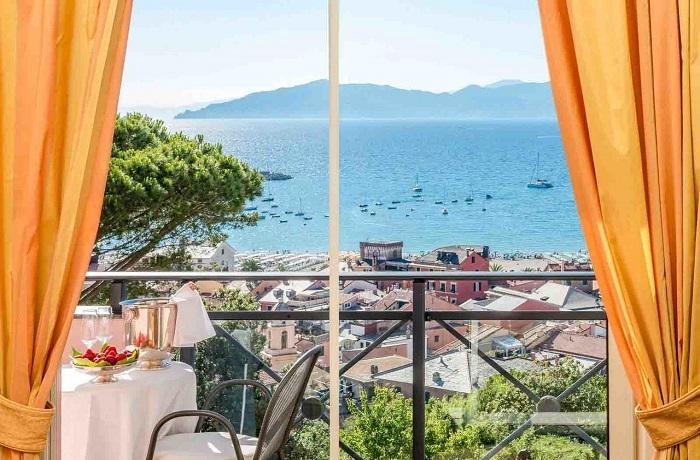 Badeurlaub: Balkon mit Aussicht auf das Meer und die Berge vom Hotel Vis À Vis in Ligurien, Italien