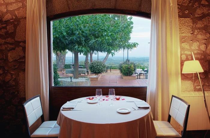 Hotels in Spanien: Can Xiquet, Cantallops, Romantisches Restaurant, weißer gedeckter Tisch, mit Blick zur Terrasse und grüner Landschaft