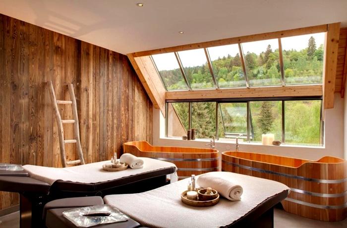 We llnesshotels: Hostellerie La Cheneaudière & Spa - Elsass, Frankreich mit Massageliegen und Blick aus dem Fenster auf Wälder
