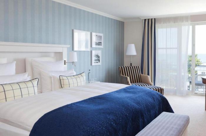 Hotelzimmer im Steigenberger Grandhotel & Spa auf Usedom mit Bett und Blick auf die Terrassentür.