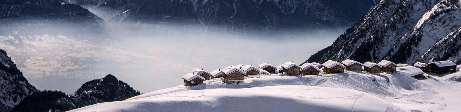 """Titelbild """"Winterurlaub: 12 Skihotels in Pistennähe"""". Hier zu sehen: Blick auf Hütten und Berge im Nebel."""