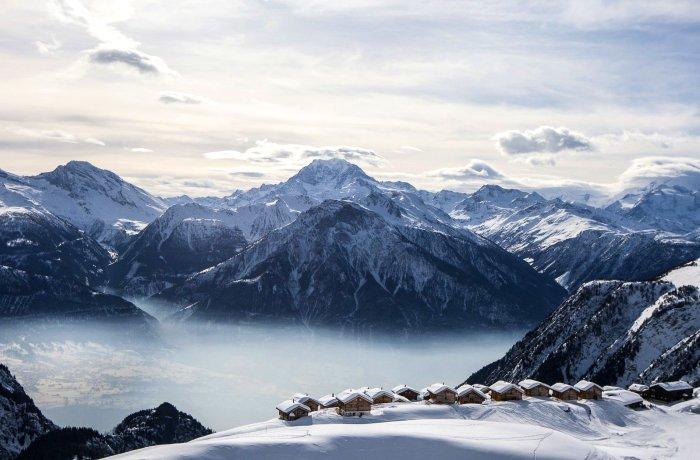 """Titelbild für """"Winterurlaub: 12 Skihotels direkt an der Piste"""". Zu sehen: Blick auf die Hütten und das Bergpanorama der Hamilton Lodge & Spa im Wallis"""