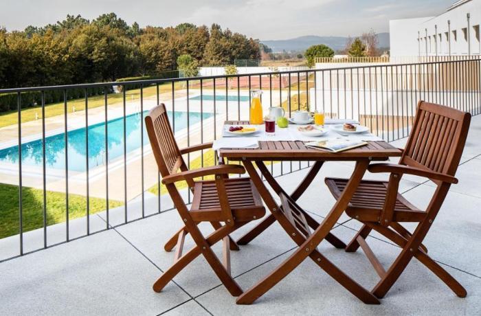 Terrassentischchen und Stühle: Frühstück auf der Terrasse im Hotel Minho in Portugal vor Poolkulisse