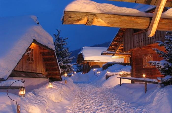 Laternen beleuchteter Weg voller Schnee zwischen Holzchalets  bei Abenddämmerung