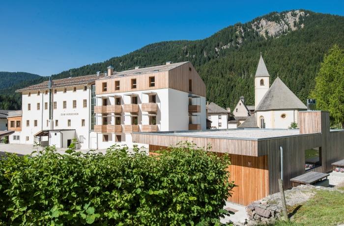 Hotel Zum Hirschen in Südtirol: Sonnige Außenansicht vom Hotel vor Bergkulisse