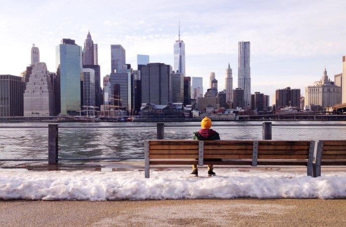 Silvesterurlaub in News York: Person sitzt auf einer Bank und schaut aufs Wasser uns Skyline von New York