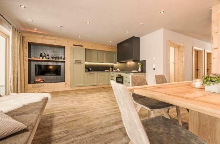 Apartment aus Holz mit grüner Designer Küche und Kamin