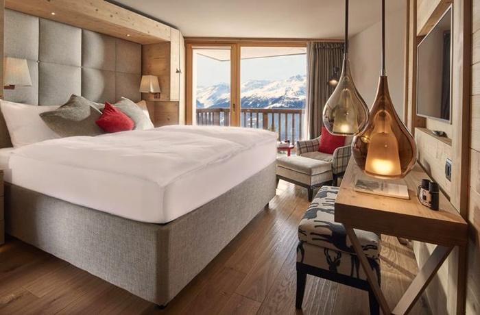 gemütliches Chalet Zimmer mit grauem Boxspringbett und roten Kissen und Balkonausblick auf die Berge