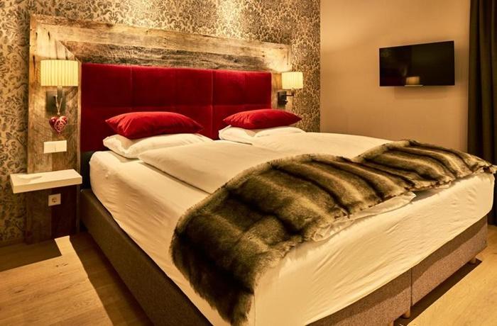 Zimmer mit Boxspringbett mit roten Elementen und Felldecke, sehr warmes Licht und gemütliche Atmosphäre