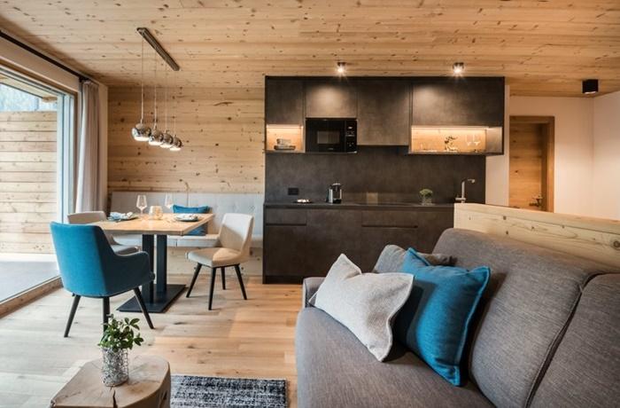 Moderne schwarze Küche und Esszimmer Bereich eines Holzchalets mit stilvollen Stühlen und Kissen