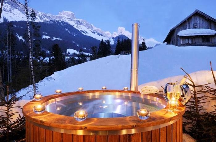 beleuchteter Whirlpool im Garten voller Schnee mit Ausblick auf die Berge