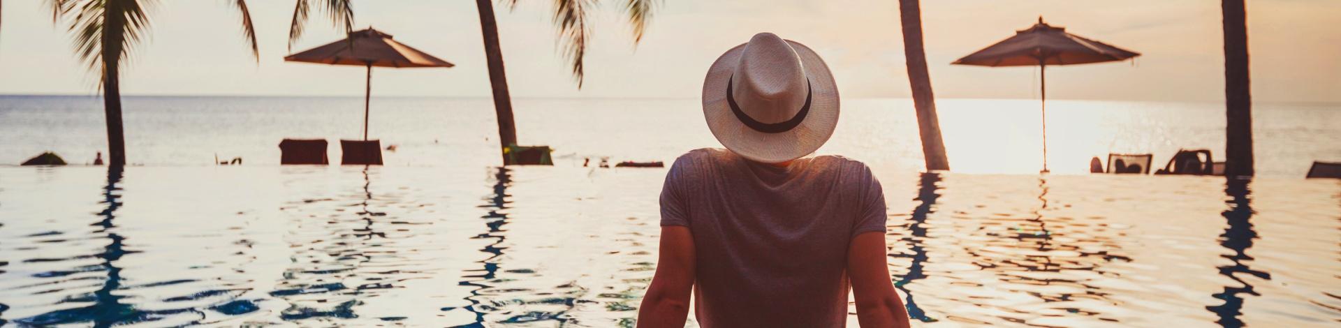 Die Top 50 männlichen Reiseblogger: Mann mit Hut schaut auf Pool und Palmen
