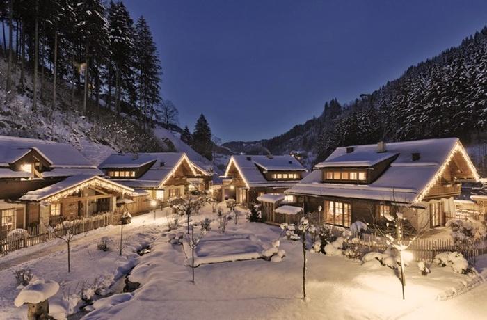 Dorf aus schneebedeckten Chalets, umgeben von Wäldern bei Nacht