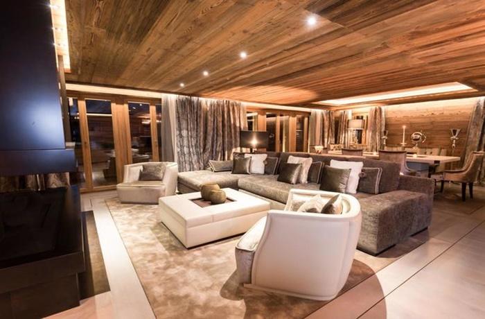 glamouröses Wohnzimmer mit großem gemütlichen Sofa und Sesseln, Esszimmertisch und warmer Beleuchtung