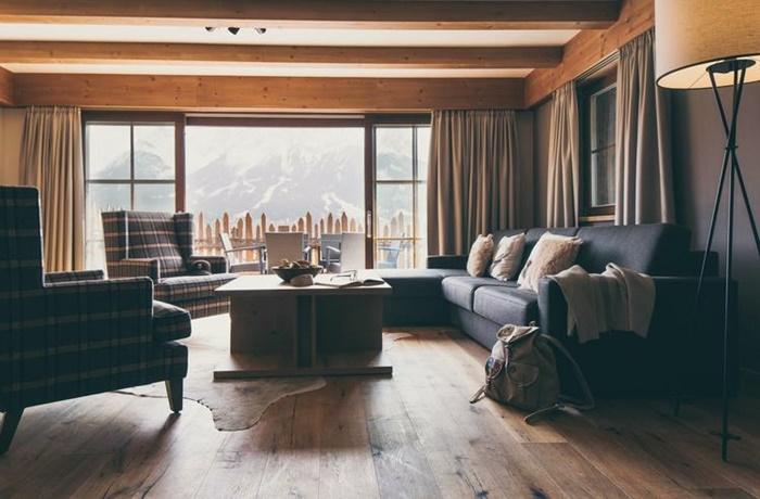 Wohnzimmer eines Chalets mit karierten Sesseln und schwarzem Sofa, Holzboden und Holzbalken, Balkon mit Ausblick auf die Berge